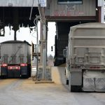 A truck picks up a load of distillers grain on the left and another drops of a load of corn on the right at the Greenfield Global ethanol plant